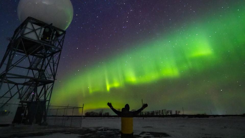 Une personne de dos se tient les bras tendus vers le ciel en face d'une aurore boréale.