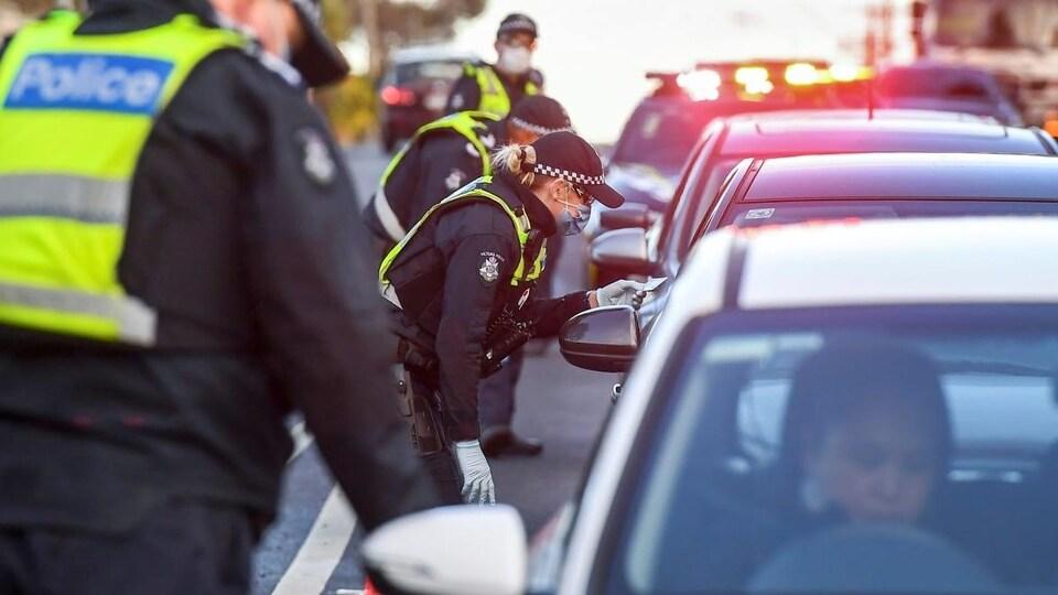 Les policiers vérifient les lieux de résidence des automobilistes sur leur permis de conduire dans un barrage routier en banlieue de Melbourne au mois de juillet.