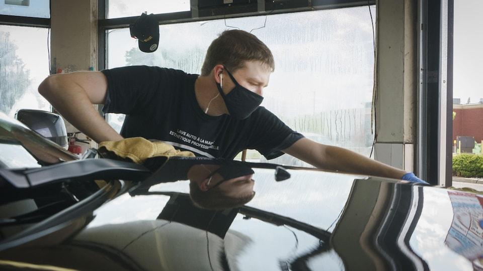 Un jeune homme travaille dans un lave-auto avec des écouteurs dans les oreilles et un couvre-visage.