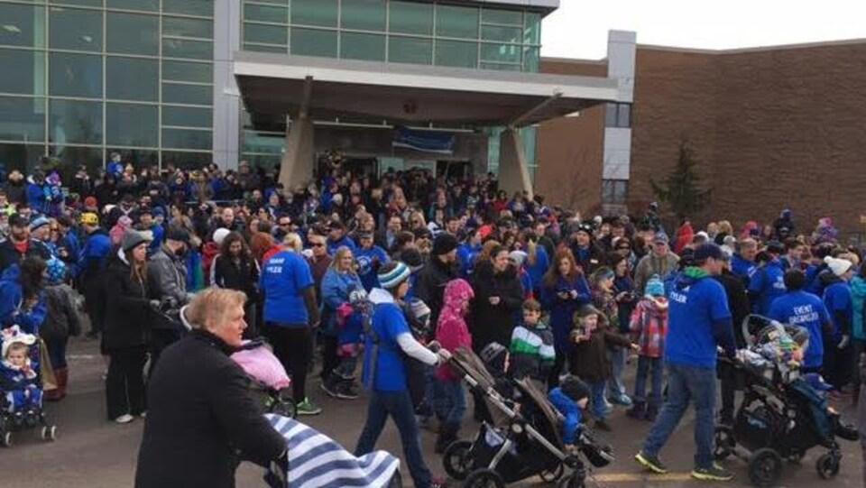 Des centaines de personnes vêtues de gilets bleus marchent ensemble