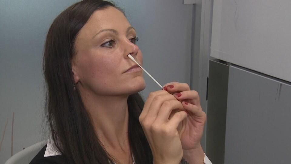 Une femme entre un écouvillon dans son nez.