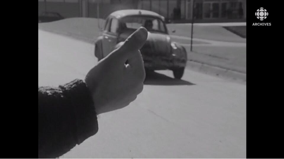 Gros plan du bras d'un homme qui tend le pouce en bordure de rue.