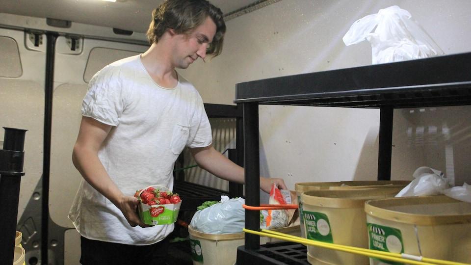 Un homme est en train de classer des fraisons dans un camion de livraison.