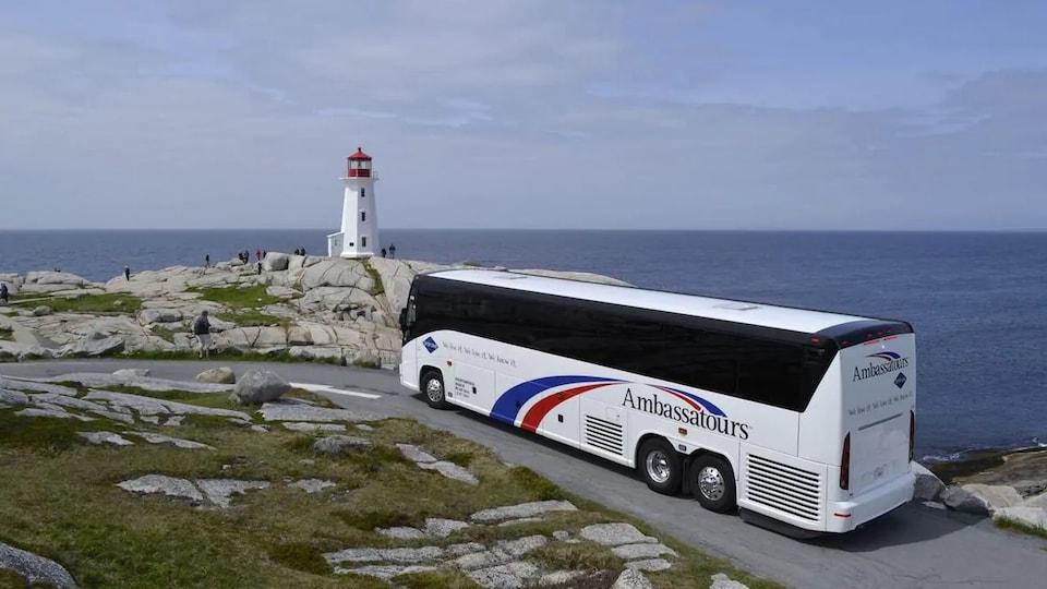 Un autocar de tourisme devant le phare de Peggy's Cove.