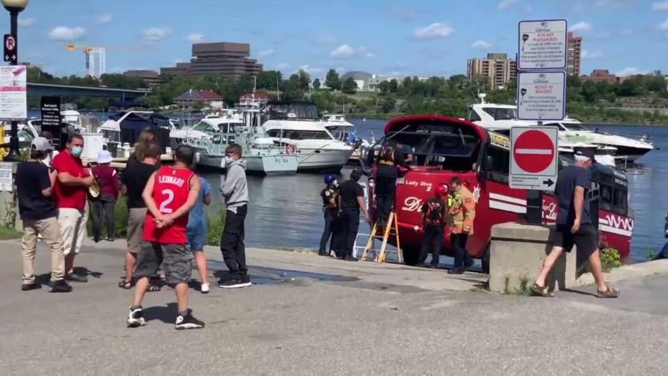Un autobus stationné au bord de l'eau pendant que des premiers répondants aident des personnes à en sortir.