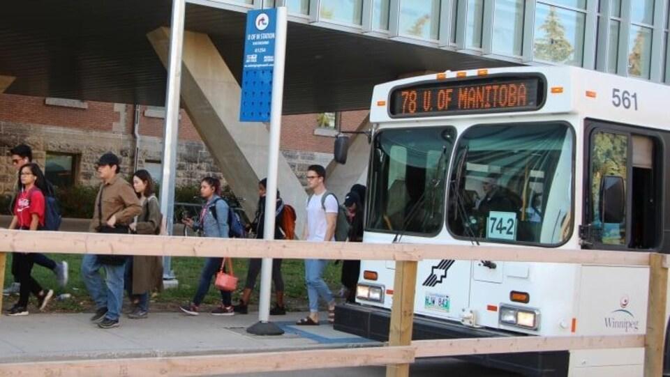 Des étudiants descendent d'un autobus.