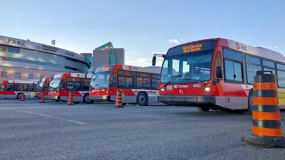 Des autobus d'OC Transpo dans le stationnement d'un stade sportif le matin.