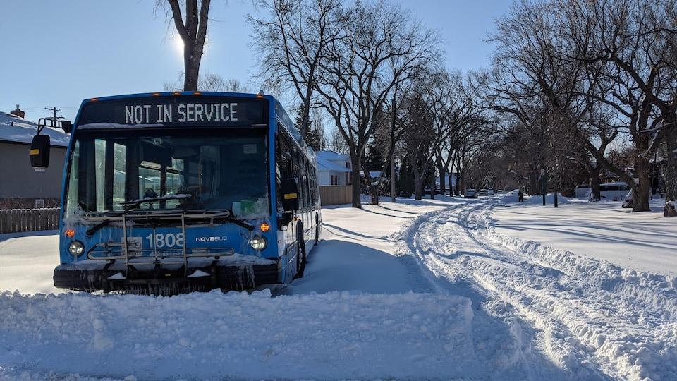 Un autobus de Saskatoon Transit hors service est entouré de plusieurs centimètres de neige au plein au milieu d'une rue de Saskatoon.