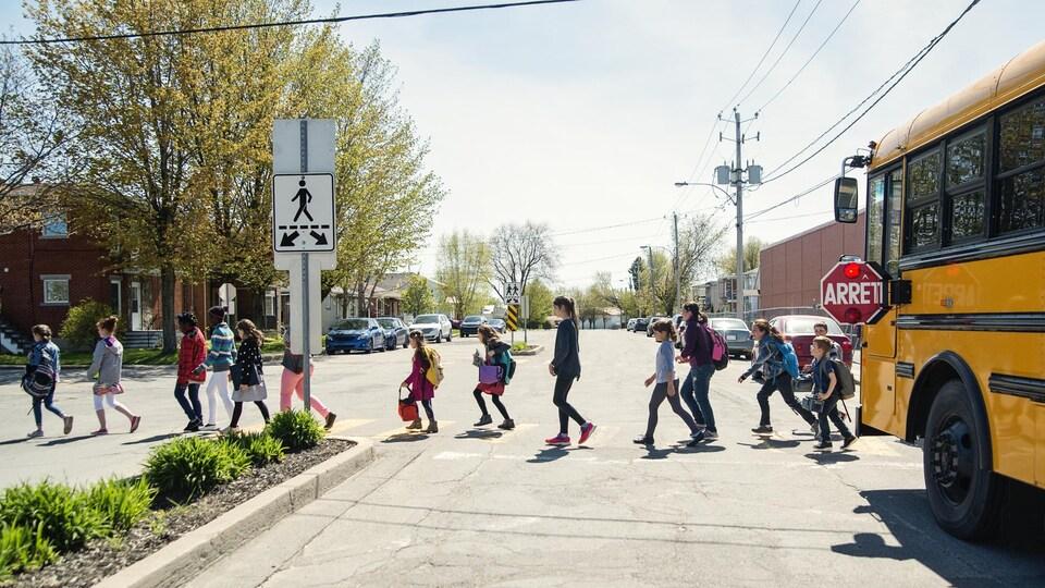 Des enfants traversent la rue après être descendus d'un autobus scolaire.