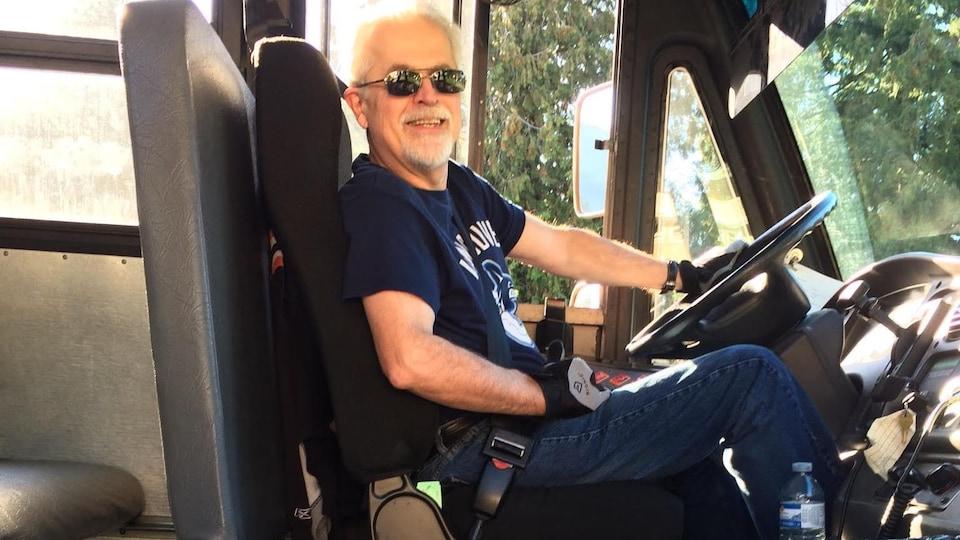 Un homme assis sur le siège de conducteur d'un autobus regarde la caméra