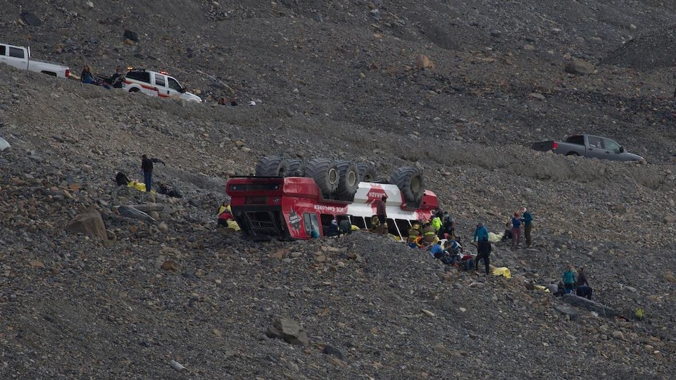 Un autocar complètement renversé et sorti de la route dans une montagne. Le toit du véhicule est sur des roches. Beaucoup de personnes sont autour de lui.
