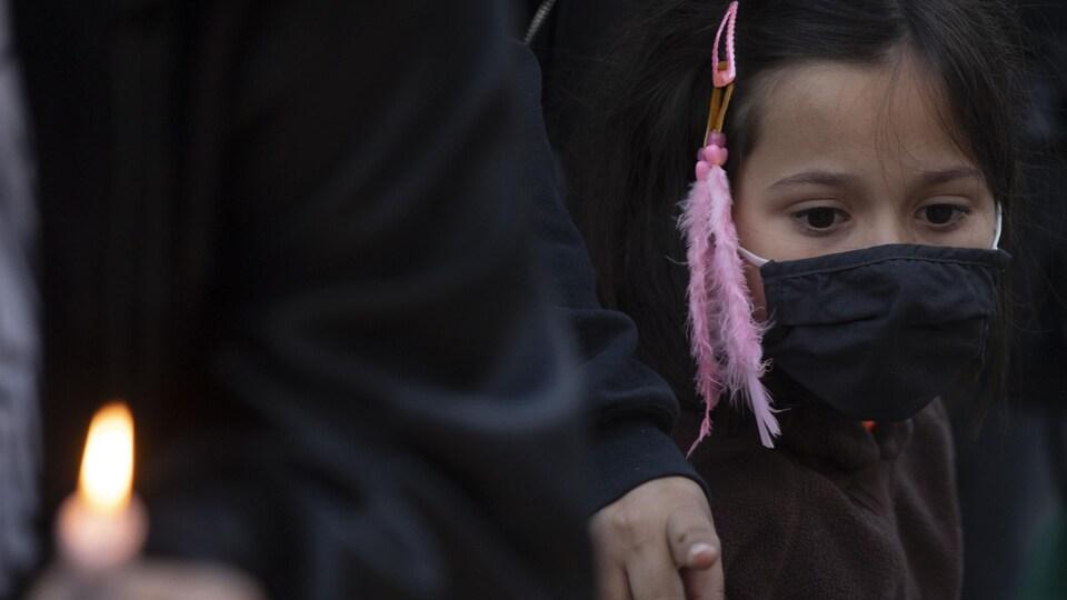 Une jeune autochtone assiste à une veillée à la chandelle pour rendre hommage aux pensionnaires autochtones.