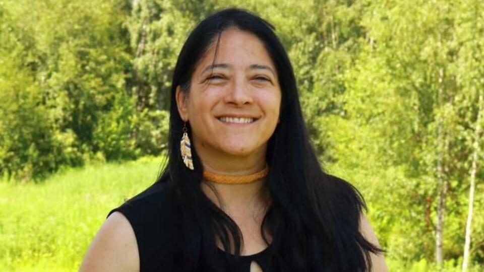 Une femme autochtone, dans un boisé, sourit.