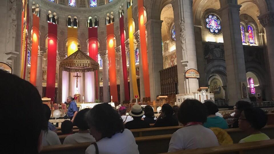 Des chrétiens sont assis à la basilique de Sainte-Anne-de-Beaupré.