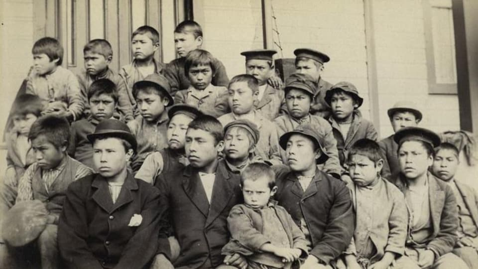 Une vieille photo dépeignant un groupe d'une dizaine de jeunes garçons autochtones devant un bâtiment.