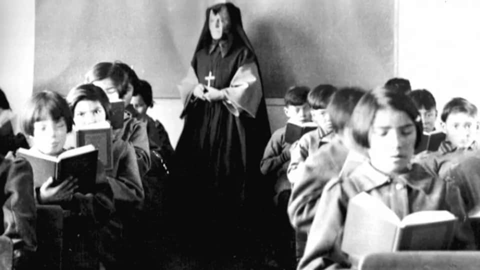 Photo historique dans une classe du pensionnat Sainte-Anne où l'on peut voir de jeunes Autochtones en train de lire et une religieuse au fond de la pièce.