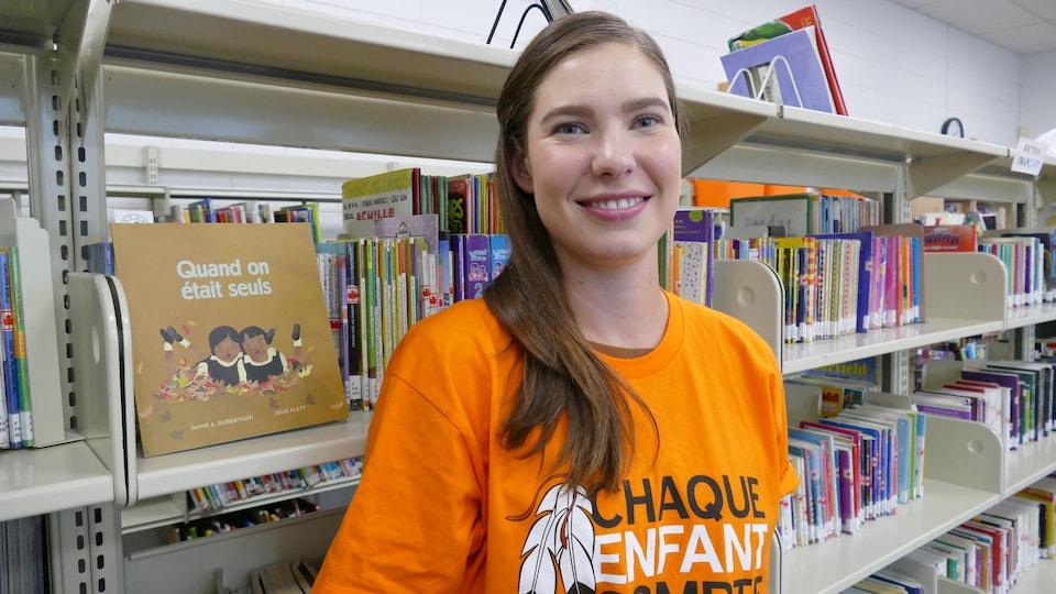 Renée Martel enseignante porte un chandail orange et se tient debout dans la bibliothèque.
