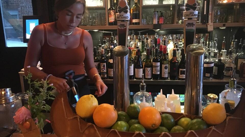 Une serveuse travaille derrière un comptoir où est posé un bol à fruits en forme de canot traditionnel.