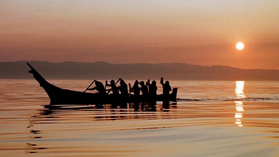 Des pagayeurs au lever du soleil.