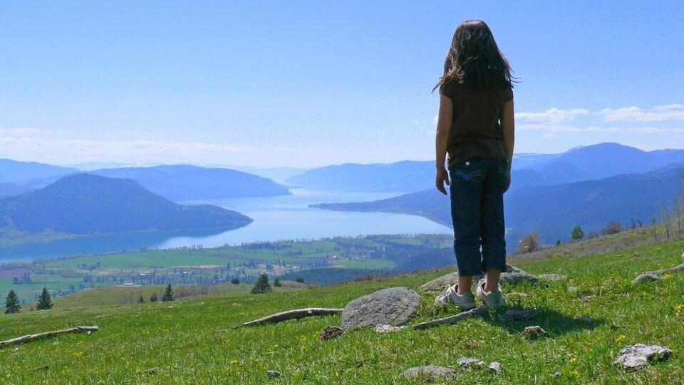 Un jeune regarde un paysage montagneux.