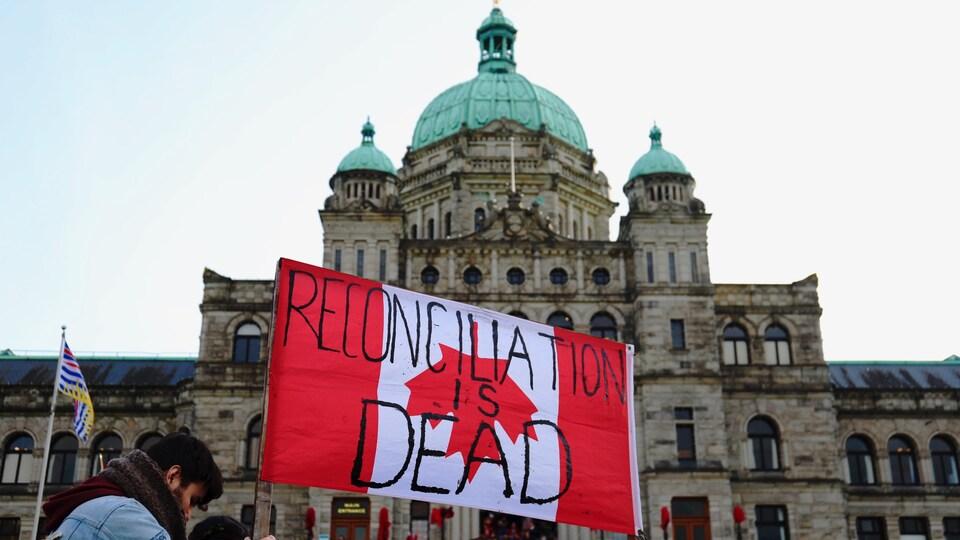 «La réconciliation est morte» lit-on sur un drapeau canadien, porté par un manifestant devant l'Assemblée législative de la C.-B.