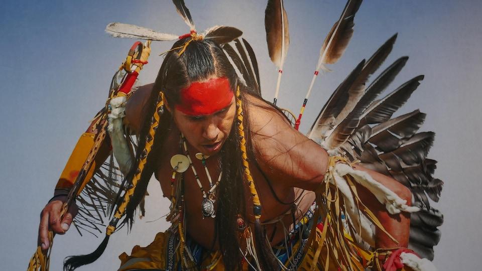 Une photo d'un Autochtone lors d'une cérémonie pow-wow où les communautés se retrouvent pour honorer la mémoire de leurs ancêtres et remercier la vie.