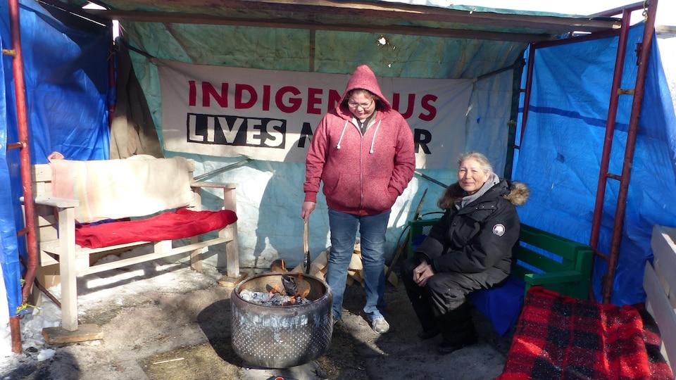 Richelle Dubois et sa mère se tiennent auprès du feu dans une tente du camp de protestation érigé face à l'Assemblée législative de la Saskatchewan.