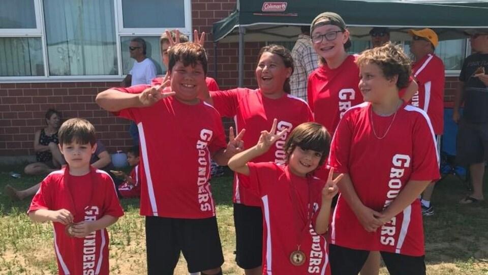 Des enfants de la Première Nation d'Eel Ground vêtus de rouge montrent leurs médailles après leur match de soccer.