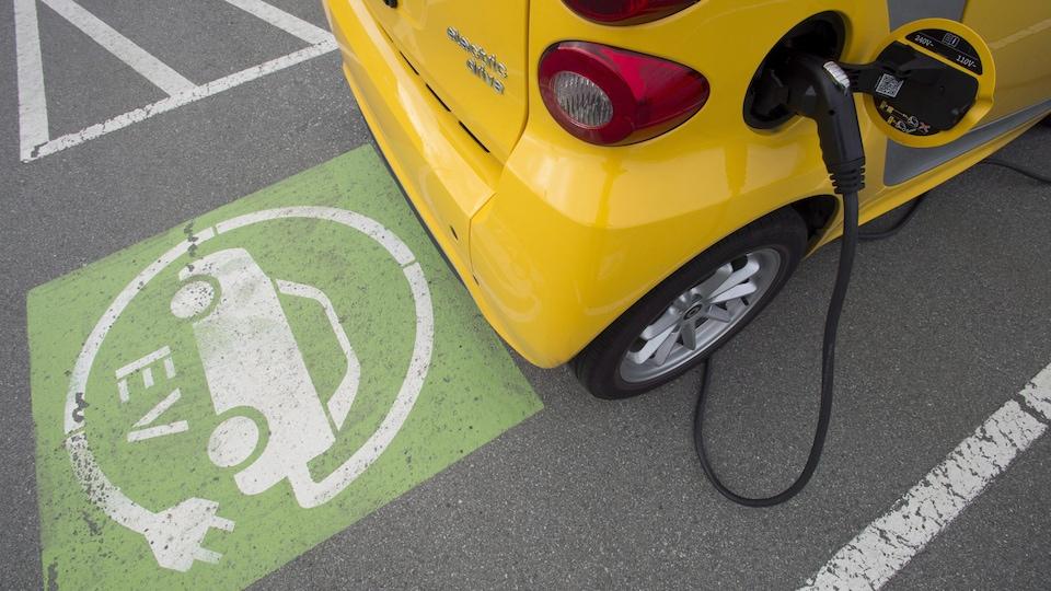 Une petite voiture électrique est rechargée dans un stationnement.