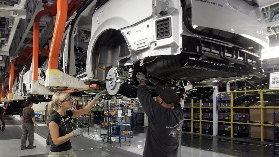 Un homme et une femme travaillent dans une usine d'assemblage du groupe Fiat Chrysler Automobiles.