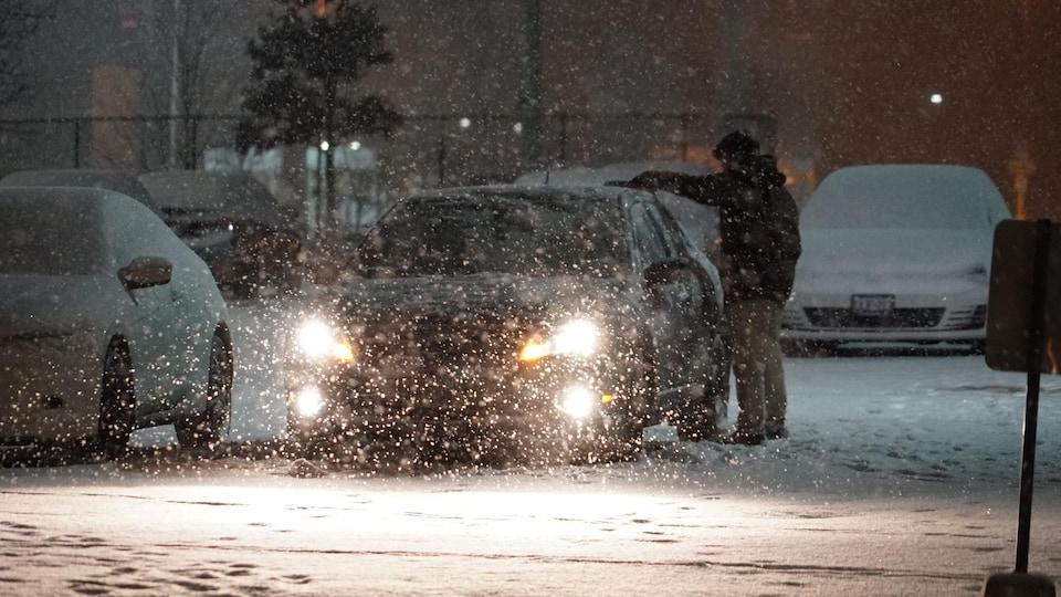 Un automobiliste déneige sa voiture.