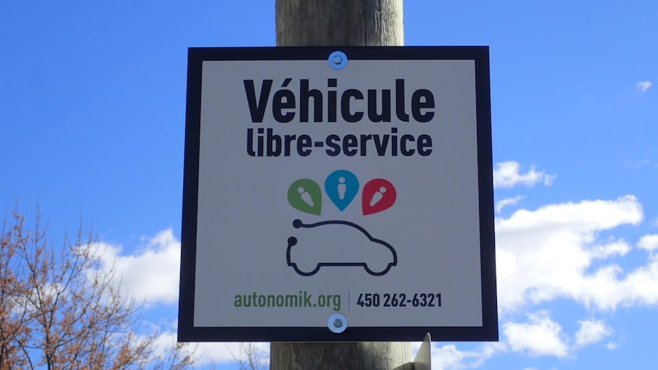 Une affiche indique l'endroit où est stationnée la toute première voiture en libre-serve d'Autonomik.