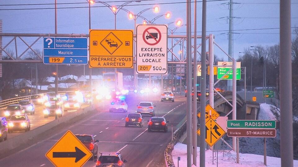 Voitures et camions qui circulent sur le pont à l'heure où le soleil se couche