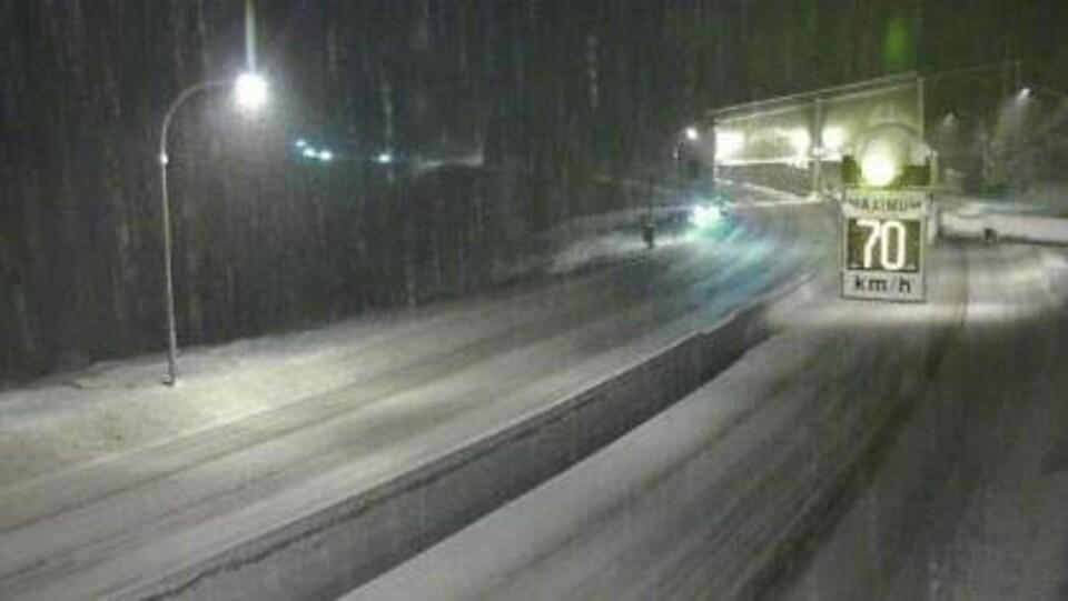 Une route avec un lampadaire allumé, de la neige sur la chaussée, il fait sombre, un panneau limite la vitesse à 70 km/h.