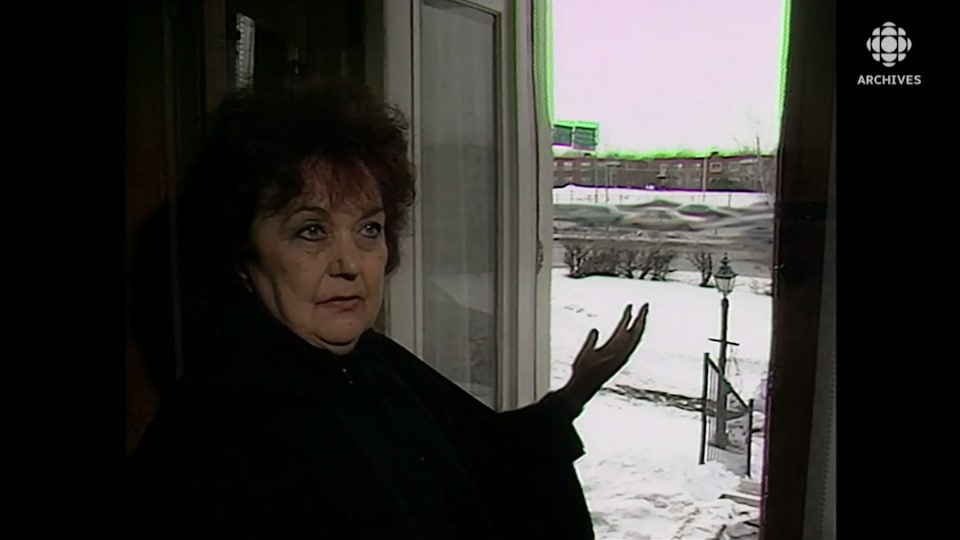 Une femme devant sa porte montre l'autoroute qui passe devant sa maison.