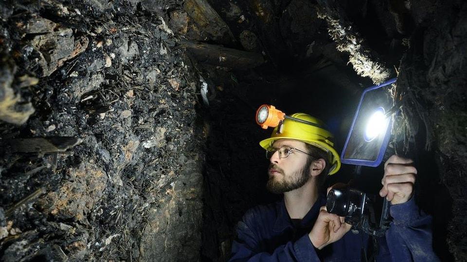 Un chercheur inspecte le mur d'une mine.