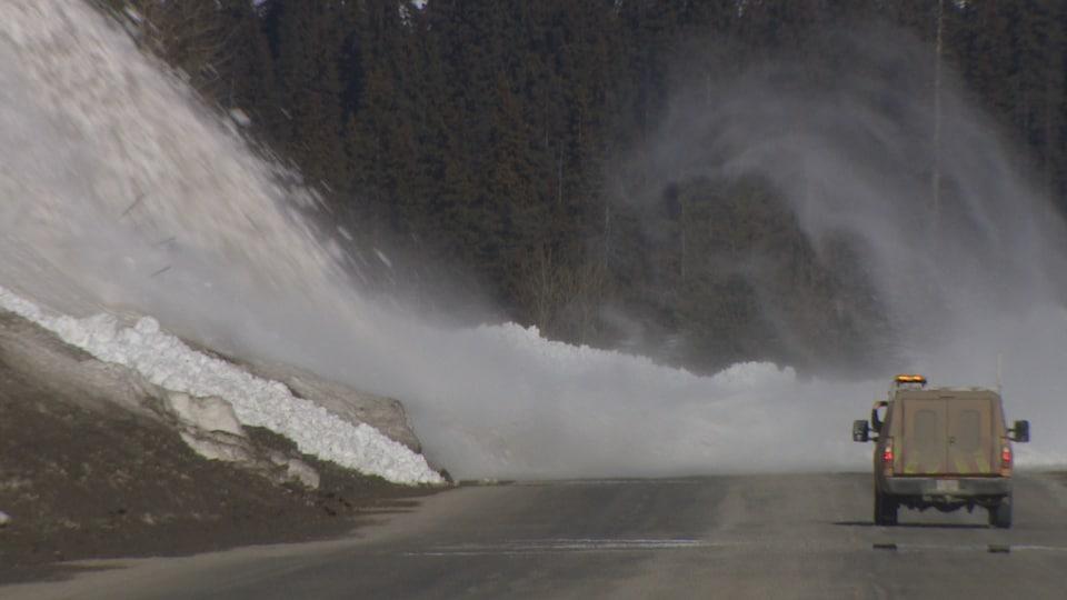 La neige finit sa trajectoire sur l'asphalte et un véhicule se tient à distance