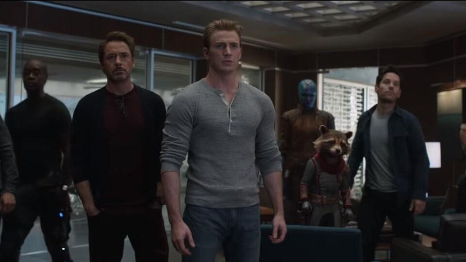 Huit superhéros sont debout dans une pièce et rengardent quelque chose qui est hors-champ.
