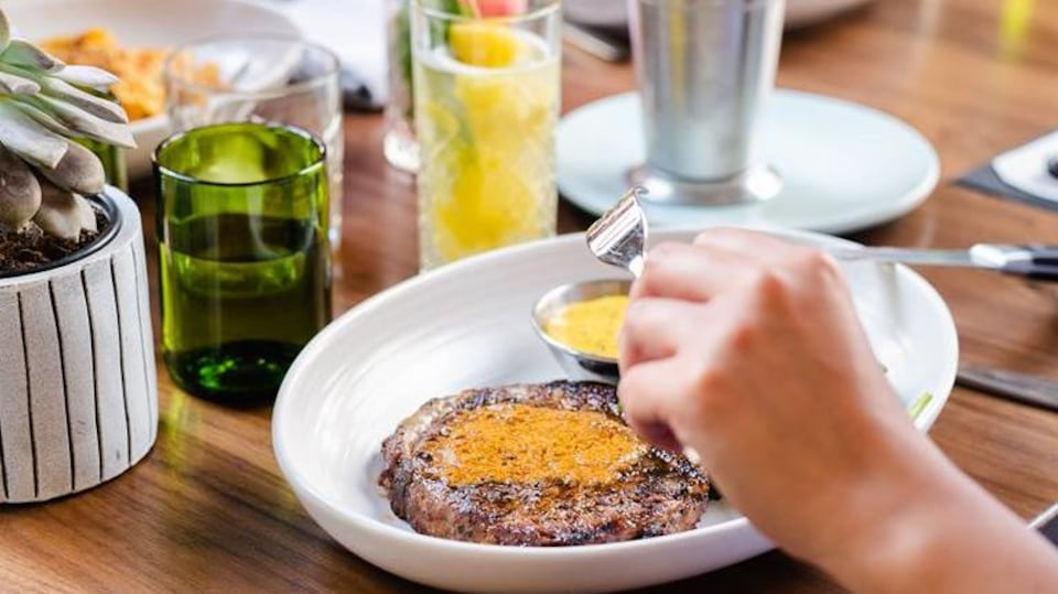 Des clients mangent de la viande et des frites à une table.