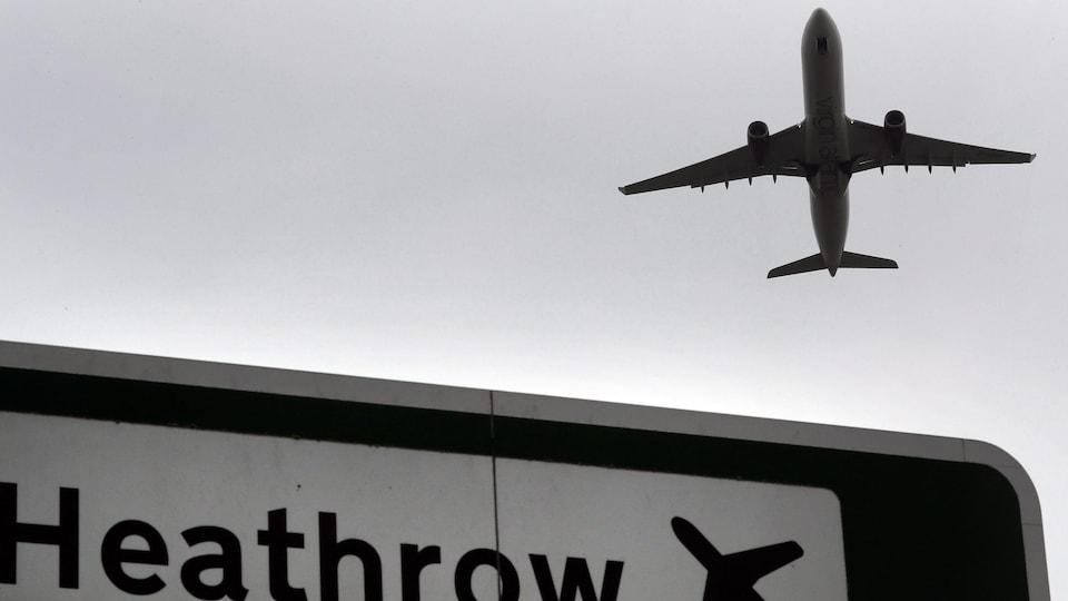 Un avion vole au-dessus d'une pancarte sur laquelle on peut lire le nom de l'aéroport.
