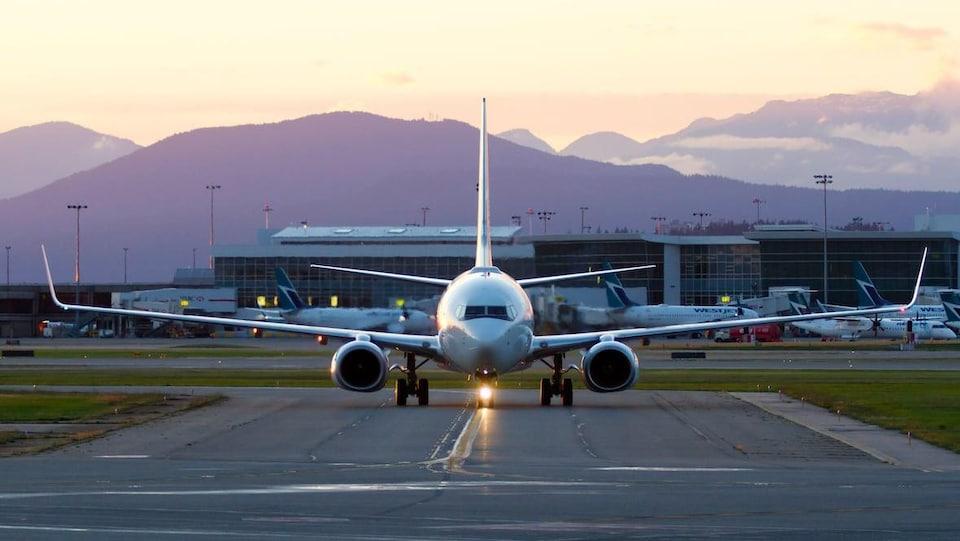 Un avion sur la piste. Des montagnes pourpres et un lever de soleil derrière.