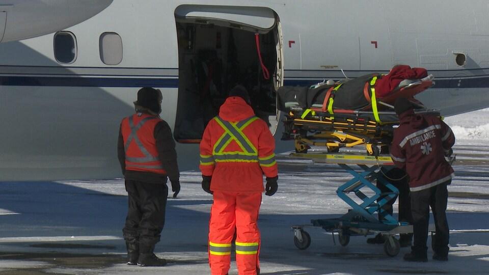 Patient sur une civière qui entre dans l'avion