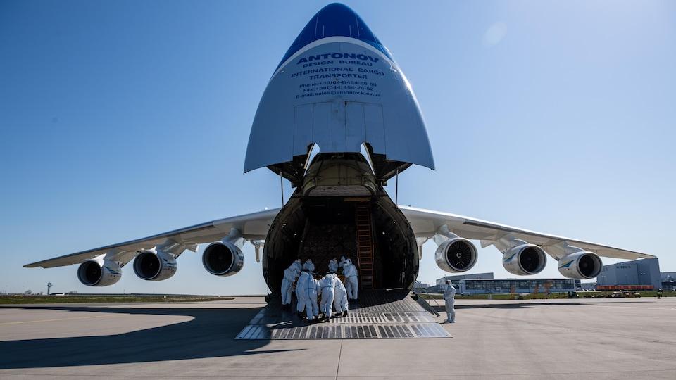 Des employés déchargent le contenu d'un avion sur le tarmac d'un aéroport.