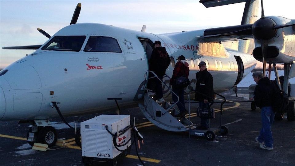 Des travailleurs prennent l'avion à l'aéroport de Bathurst.