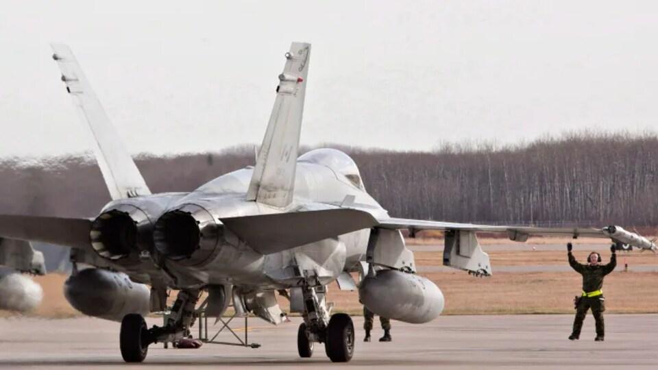 Un avion militaire CF-18 sur le tarmac d'une base militaire.