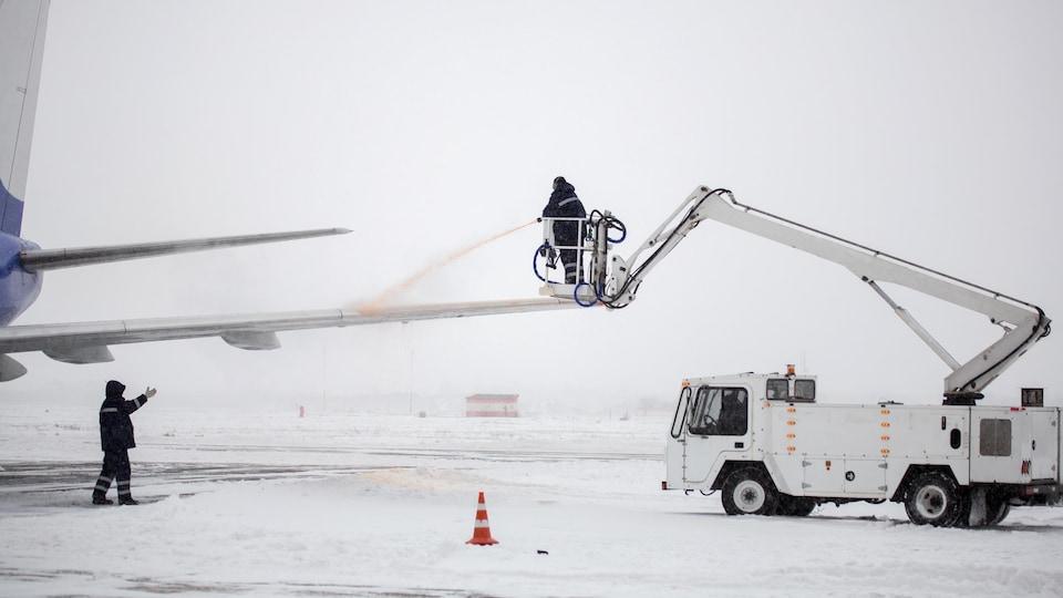 Un employé d'un aéroport applique du liquide de déglaçage sur un avion.