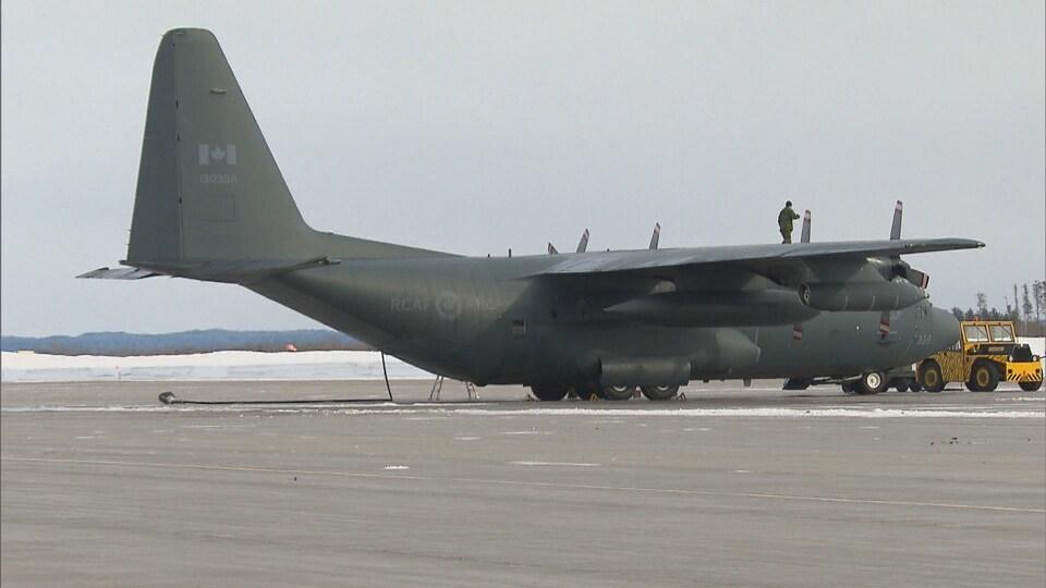 Avion Hercules sur le tarmac avec un technicien sur une aile.