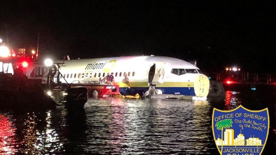 Un avion est immobilisé dans l'eau. Des équipes de secours s'activent autour de l'appareil.