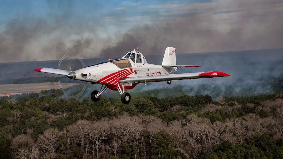 Un avion blanc et rouge vole dans la fumée d'un feu de forêt qu'on peut appercevoir au loin.