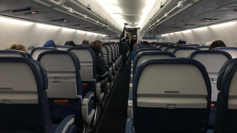 On voit de dos les sièges de l'avion, qui sont peu occupés.